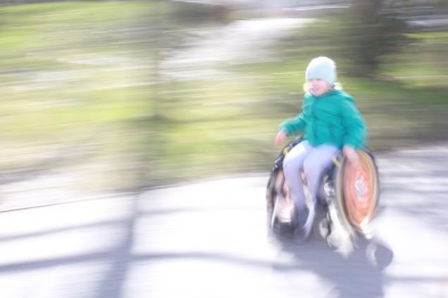 Auf dem Bild ist ein Kind im Rollstuhl zu erkennen, dass von rechts nach links fährt. Offenbar mit hoher Geschwindigkeit, da die Umgebung stark verzerrt ist.