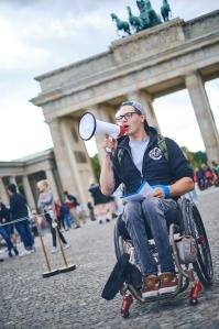 ein weißer Rollstuhlfahrer steht mit Megaphon vor dem Brandenburger Tor