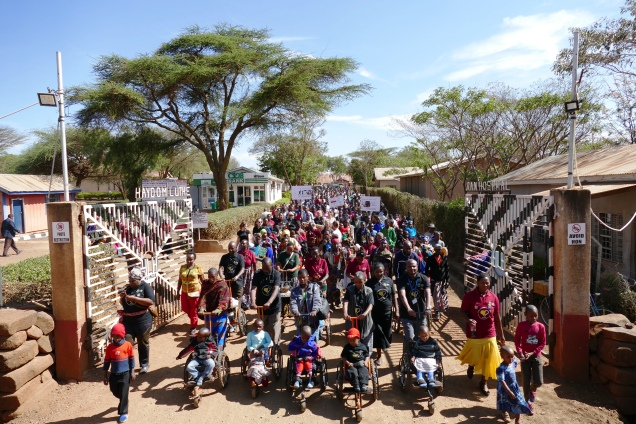 Auf dem Bild verlässt eine große Menschenmenge die Tore der Klinik in Haydom, ganz vorne Kinder im Rollstuhl.