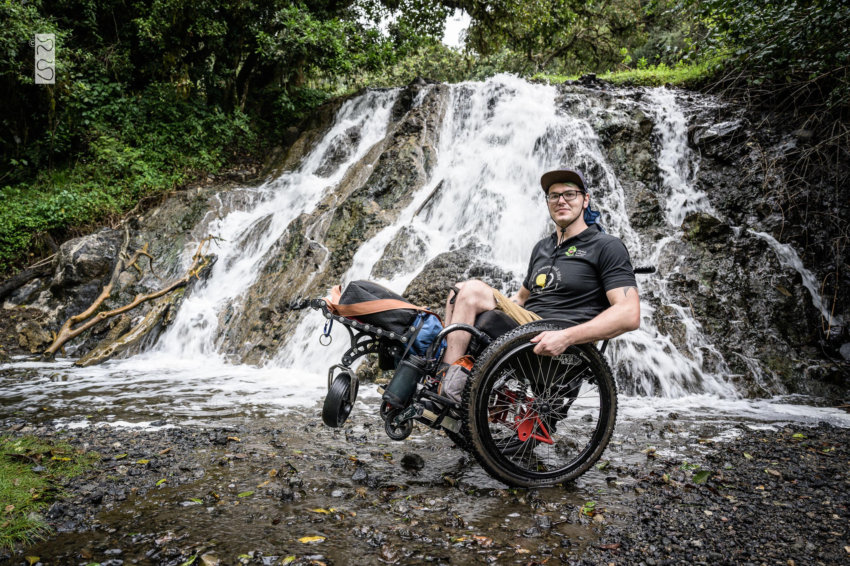 David posiert mit seinem Rollstuhl vor einem Wasserfall