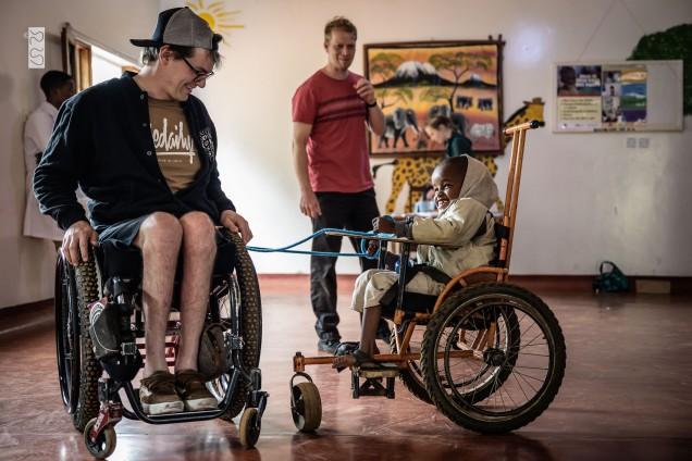 David zieht ein kleines Kind im Rollstuhl mit einem Seil