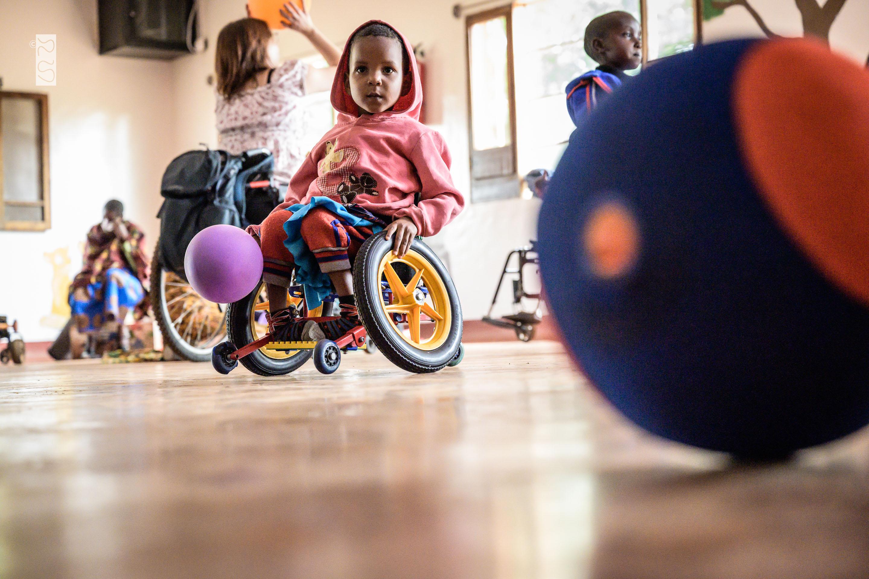 Ein kleines Mädchen sitzt in einem Rollstuhl und jagt nach Bällen