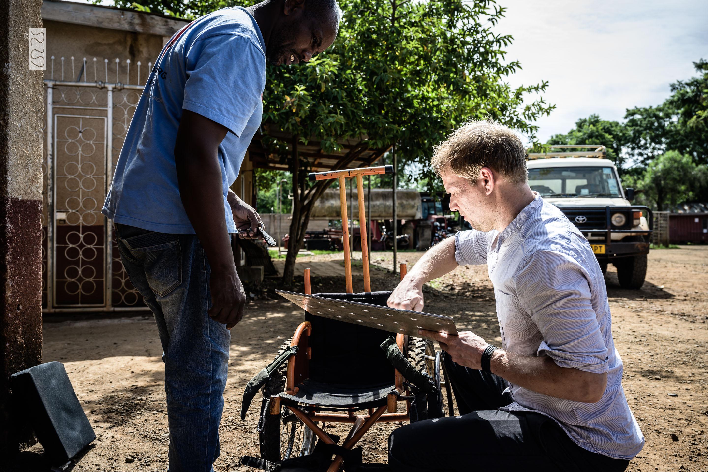 Jens mit dem Schrauber aus Haydom arbeiten am Rollstuhl von Musa