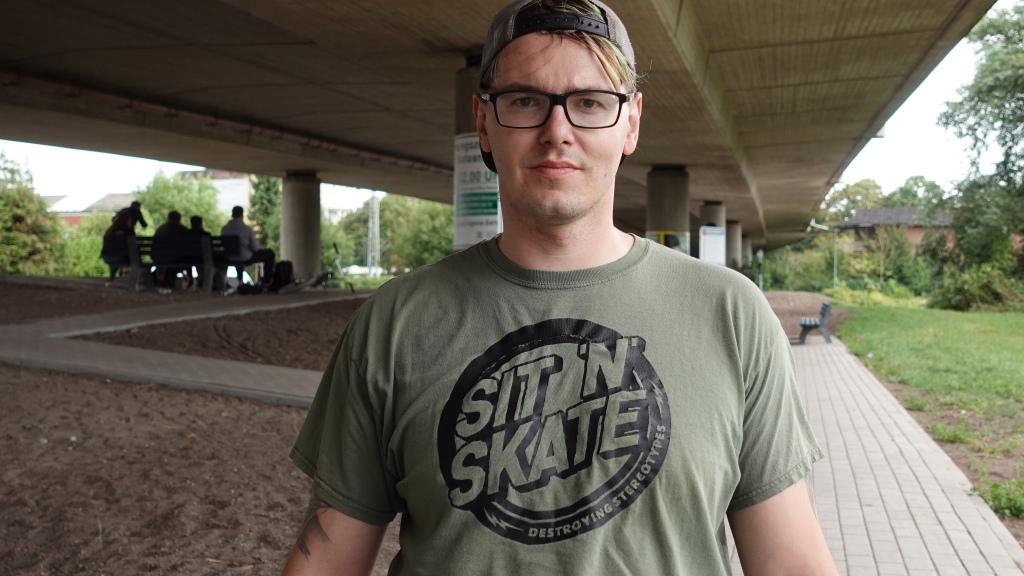 Ein weißer Mann steht mit einem Oliv farbenden Shirt unter einer Brücke. Auf dem Shirt steht auf Englisch Sit N Skate - Destroying Stereotypes. Im Hintergrund sieht man eine Rollstuhlrampe, eine Bank und mehre Menschen darauf. Eine weitere Bank ist leer.