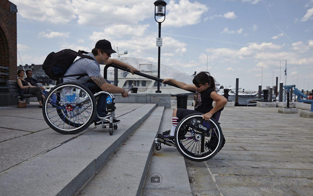 Ein weißer Rollsuhlfahrer steht oben an einer Treppen und reicht die Hand zu der weißen Rollstuhlfahrerin die unten versucht die Stufe hoch zu kommen.